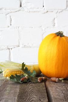 木製のテーブル、白いレンガの背景に秋のカボチャと他の野菜