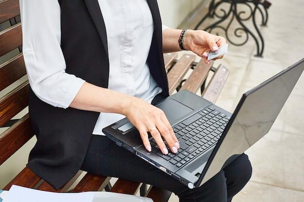Ноутбук и банковская карта в руках крупным планом.