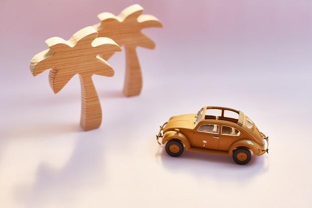 ピンクの背景に黄色のレトロなカブリオレのおもちゃの車とヤシの木。