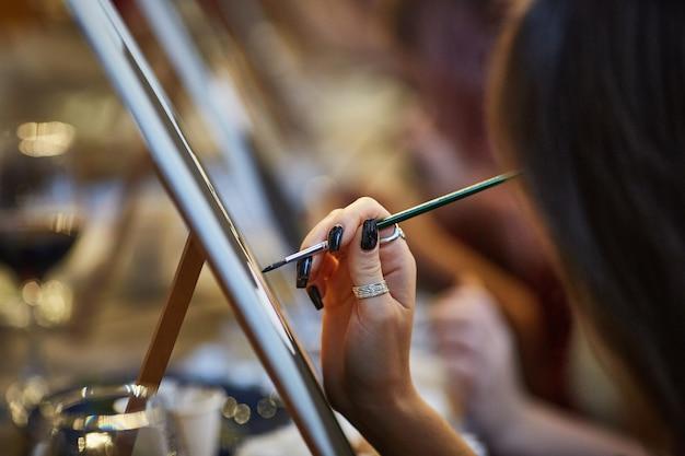 Крупный план руки художника-женщины, рисующего картину
