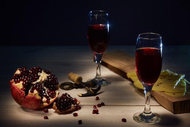 Бокалы свежего гранатового вина, спелый гранат. сыр на доске.