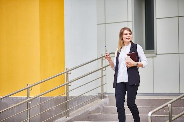 女の子は建物の階段に立っています。メモ帳、電話、ペンを持っています。教育やビジネスのコンセプト