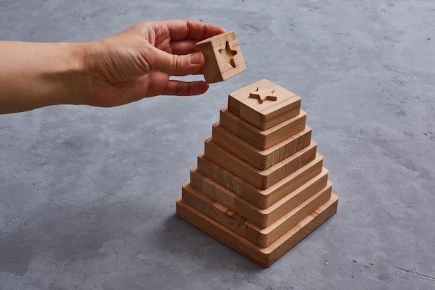 Деревянная игрушечная пирамида с геометрическими фигурами. рука безликая
