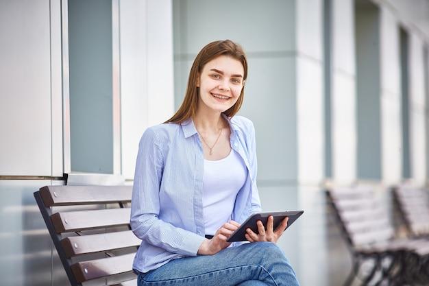 若い女の子が彼女の手でタブレットでベンチに座って、笑顔します。