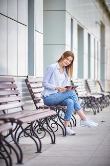 若い女の子がタブレットを手にベンチに座って、笑顔します。