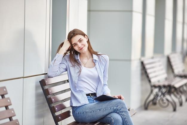 Молодая девушка сидит на скамейке с планшетом в руках и улыбается.