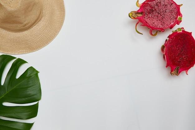 コロナウイルス中の休息の概念。コピースペースを持つドラゴンフルーツ、帽子、モンステラリーフ。フラットレイ