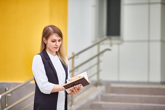 女性が建物の階段に立ってノートに書く