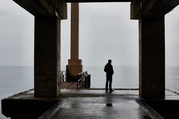 悪天候で海の桟橋に一人で立つ男。霧の空気。