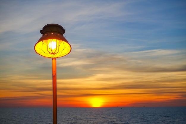 暖かいランプの照明と海での日没の照明。
