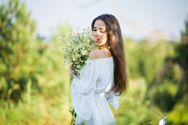 Портрет красивой молодой девушки с букетом, на открытом воздухе, в поле