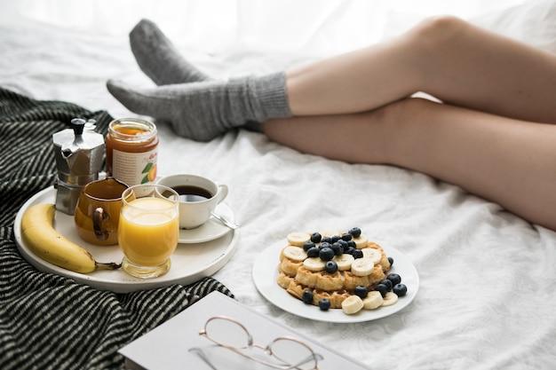 コーヒーとワッフルで週末にベッドで居心地の良い朝食のシーン