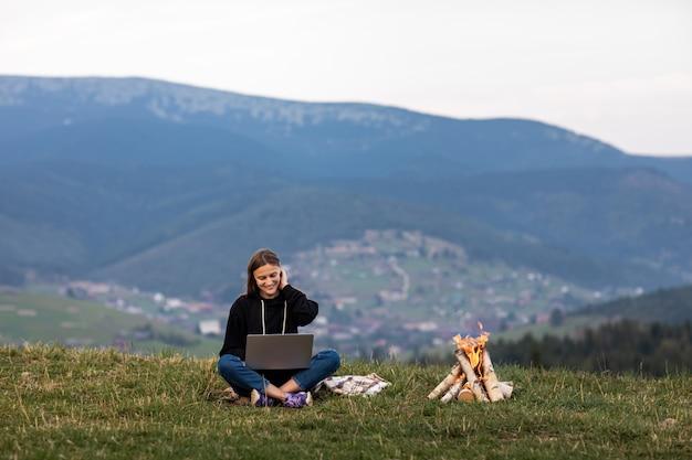 山のラップトップを持つ若い女
