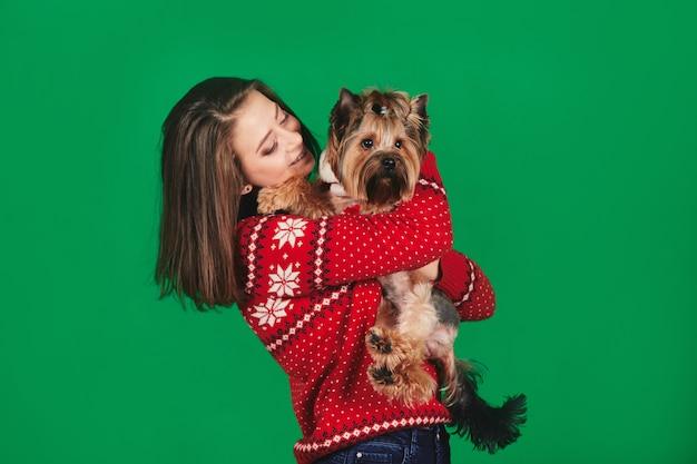 Стильная молодая женщина в рождественском свитере держит собаку