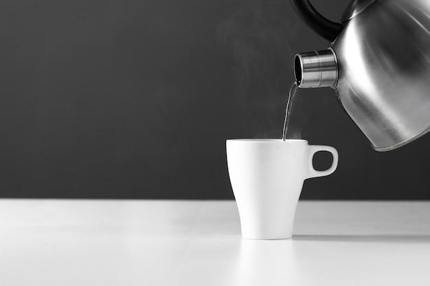 木製のテーブルの上の煙と暗い背景上のカップに水を注ぐレトロなやかん