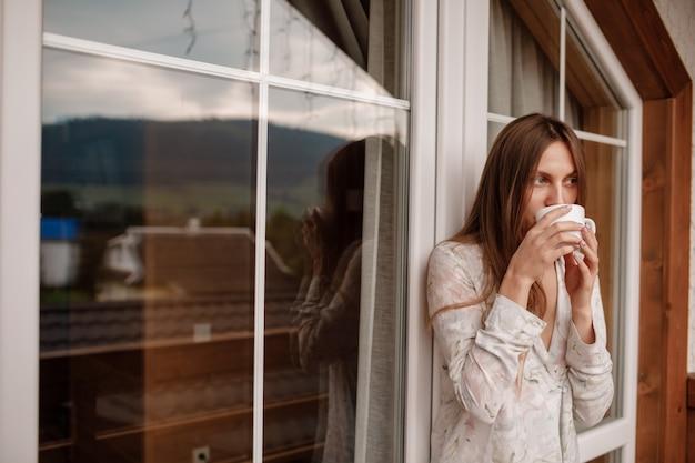 山の豪華な景色を望むホテルのテラスに立っている日を満たすコーヒーまたは紅茶のカップとスタイリッシュなナイトウェアで幸せな笑顔の若い女性の肖像画。碑文の場所