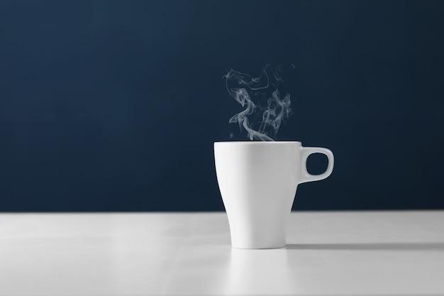 スチームと紅茶。白い円で熱いお茶。青の背景にホットコーヒーのカップ