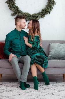 自宅で幸せなカップルを愛しています。家族、クリスマス、休日、愛と人々のコンセプト-自宅のクリスマスツリーの近くでソファに座って抱いて幸せな若い妊娠カップル。セレクティブフォーカス。
