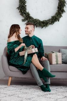 クリスマスプレゼントを開きます。幸せな愛のカップルは、クリスマス休暇のお祝いをお楽しみください。ギフトクリスマスツリーの背景を開梱しながら笑顔の愛情のあるカップルの抱擁。何の驚き。