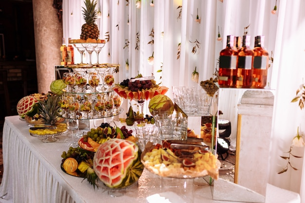Свежие, экзотические, органические фрукты, легкие закуски в тарелке на фуршете. ассорти мини деликатесов и закусок, ресторанная еда на мероприятии. награжден вкусным столом для вечеринки вкусностей.
