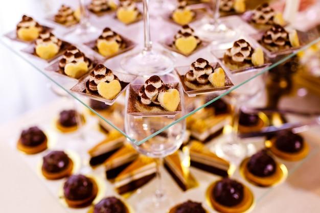 お菓子と結婚披露宴のレセプション用のカラフルなテーブル、装飾されたデザートテーブルキャンディビュッフェでおいしいお菓子パーティーのデザートテーブル。ケーキ、カップケーキ、甘さ。セレクティブフォーカス