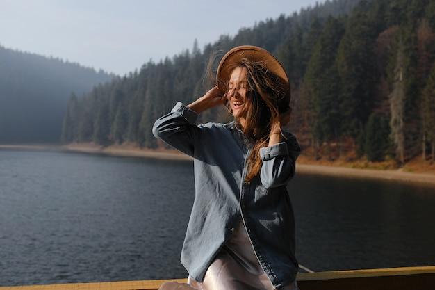 Счастливая молодая женщина в шляпе наслаждается видом на озеро в лесе. расслабляющие моменты. взгляд стильной девушки наслаждается свежестью на открытом воздухе. свобода, люди, образ жизни, путешествия и отдых