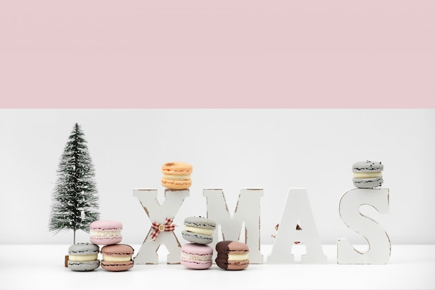 碑文のクリスマスとクリスマスの白とピンクの背景にデザートマカロンやマカロンをレンチします。食品レシピコンセプト。コピースペース。