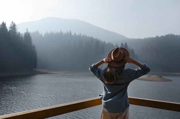 帽子の幸せな若い女性は、山の湖の景色を楽しんでいます。森でリラックスしたひととき。スタイリッシュな女の子の背面図は、屋外の鮮度を楽しんでいます。自由、人、ライフスタイル、旅行、休暇