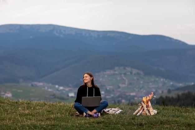 夕方には山の中でラップトップを持つ若い女性フリーランサー。キャンプファイヤーの近くに座っている観光客の女の子。