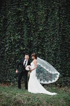 幸せな豪華な花嫁とスタイリッシュな新郎がジャンプして楽しんで、結婚式のカップル、豪華な結婚式。楽しくてクレイジーな花嫁