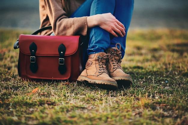 茶色の靴と暖かいコートのスタイリッシュな少女は、赤いバッグと公園に座っています。