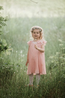 Маленькая милая девушка в розовом платье и венке из цветов на голове гуляет в лесу летом