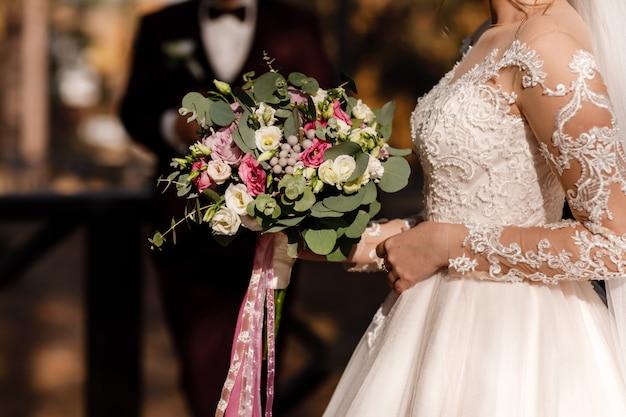 День свадьбы. жених и невеста держит букет розовых и белых цветов. свадебные украшения.