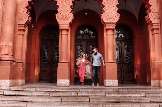 愛のヒップスターの若いスタイリッシュなかわいいカップルは、春のお城の近くの街で楽しんでいます。赤いドレスとひげを持つ男の若いブロンドの女性は、日付に笑っています。