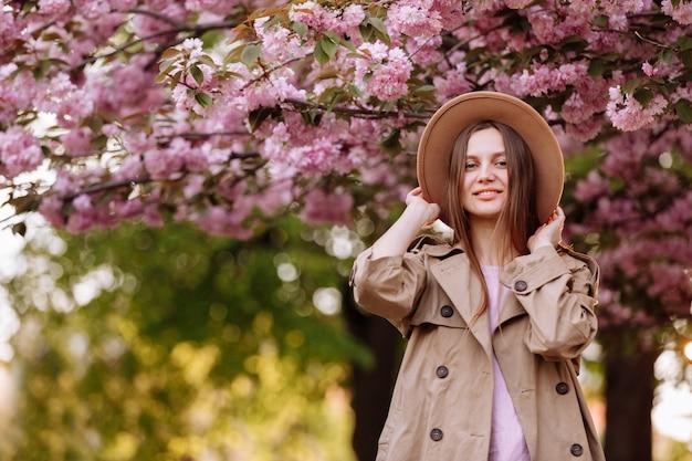 Портрет молодой красивой модной девушки в шляпе, позирует возле цветущего дерева с розовыми цветами в солнечный день