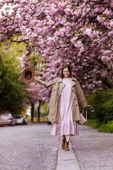 Молодая красивая стильная женщина в шляпе и розовом платье, прогулки возле сакуры цветы в парке. концепция весны. ужгород, украина