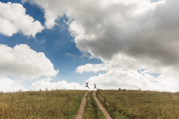 雲と青い空を背景に緑の野原でジャンプ幸せなアクティブなカップル。夏休みのコンセプト。遠くからのカップルの写真