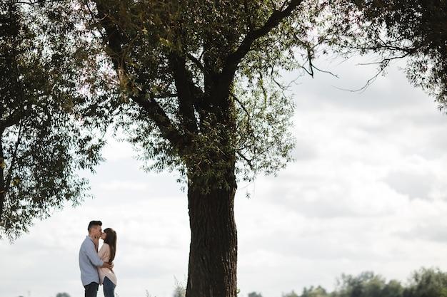 Молодая романтическая пара весело в солнечный летний день на берегу озера. наслаждаясь проводить время вместе в отпуске. мужчина и женщина обнимаются и целуются.
