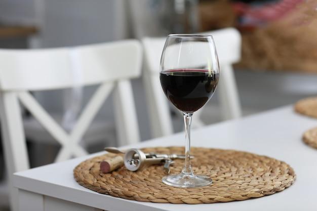 Бокал вина и некоторые винные инструменты на белой деревянной поверхности