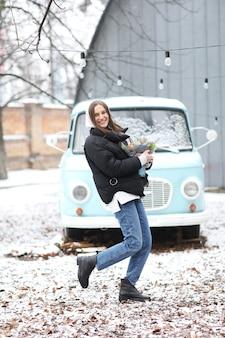 美しい若い女性は冬の公園で青いレトロな車の近くで楽しんでいます。みかんとスプルースの花束を手で作った女の子。