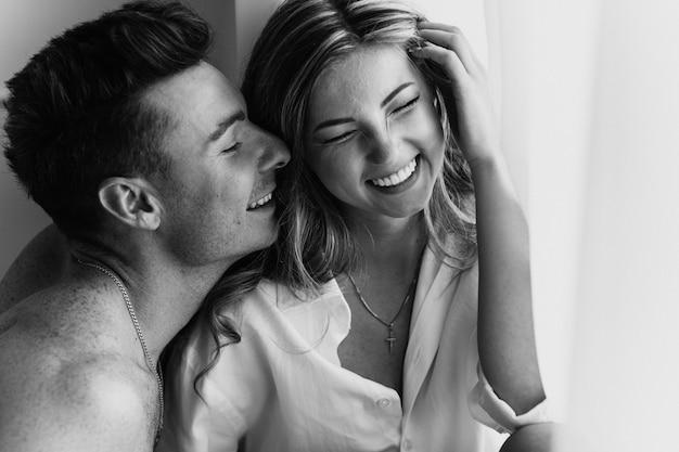Счастливая молодая любящая пара улыбается. молодая пара в любви повеселиться я в канун нового года или день святого валентина. черно-белая фотография молодой пары