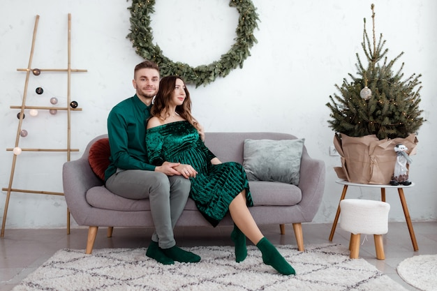 自宅で幸せなカップルを愛しています。家族、休日、愛と人々のコンセプト-自宅の木の近くのソファに座って抱いて幸せな若い妊娠カップル。