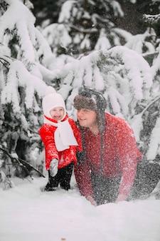 Портрет счастливой маленькой девочки в красном пальто при папа имея потеху с снежком в лесе зимы. девочка играет с папой