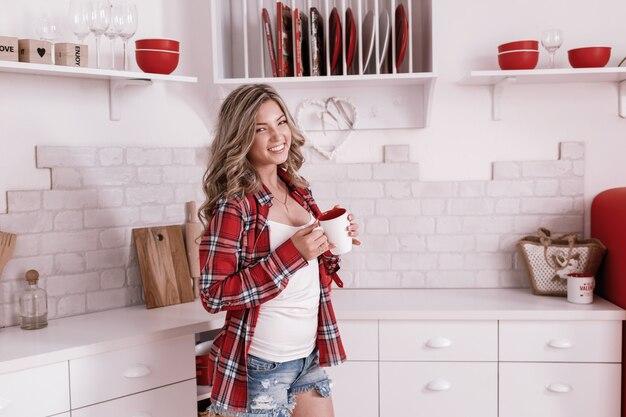 Молодая счастливая красивая женщина, пить кофе или чай на кухне в первой половине дня.