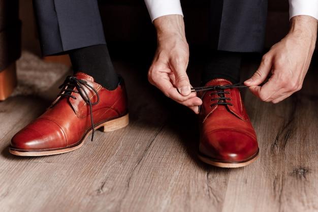 新郎が靴ひもを靴紐で縛ってください。ビジネスの男性は、ホテルの部屋で室内の靴をぶら下げています。男の手と革のメンズシューズのペア。花婿の会議。ビジネスマンの朝。