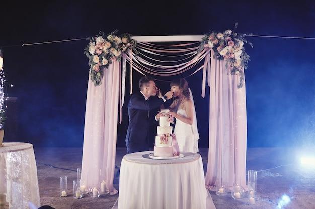ゴージャスな花嫁とスタイリッシュな新郎がスタイリッシュなウェディングケーキを味わう。ケーキ、面白い感情的な瞬間を食べて幸せな新婚カップル