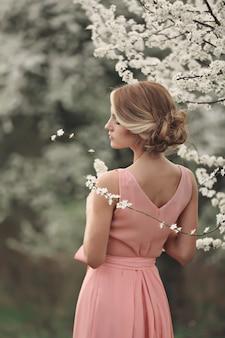 Молодая стильная женщина возле цветущего дерева в парке весны. блондинка с прической в розовом платье. фон. выборочный фокус