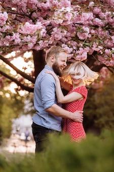 Стильная пара возле дерева сакуры. красивая молодая пара, мужчина с бородой и блондинка обнимаются и развлекаются в весеннем парке