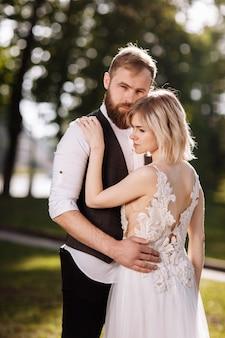 晴れた日に春の公園で抱き締めるスタイリッシュな若い美しいカップル。結婚式の肖像画。白いドレスを着た女性。