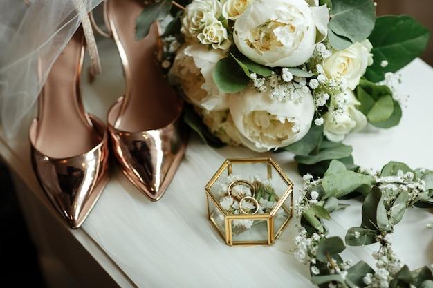Свадебные аксессуары на туалетном столике. букет невесты из белых пионов, обручальные кольца в стеклянной коробке, золотые туфли. подготовка к свадебному утру